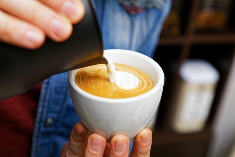 特写镜头杯子热奶咖啡 Barista举行的和倾吐的牛奶做拿铁艺术 库存图片