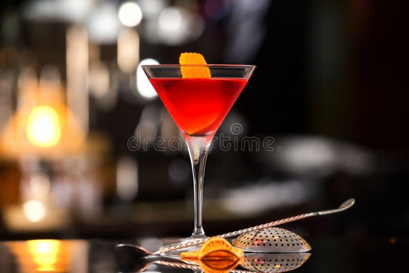 特写镜头杯曼哈顿鸡尾酒装饰用桔子 库存照片