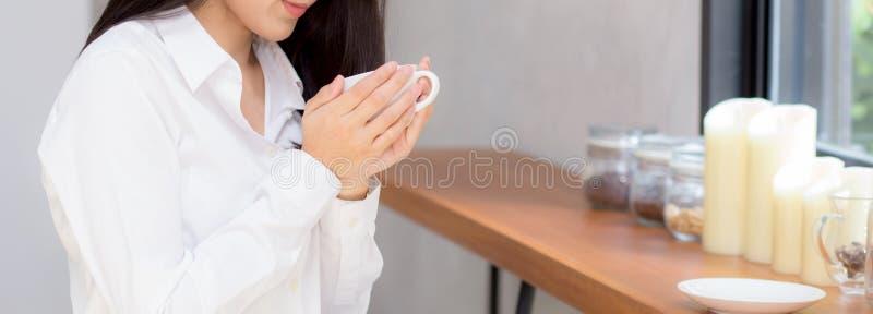 特写镜头横幅网站年轻亚裔妇女饮用的咖啡和微笑在咖啡馆的早晨 库存照片