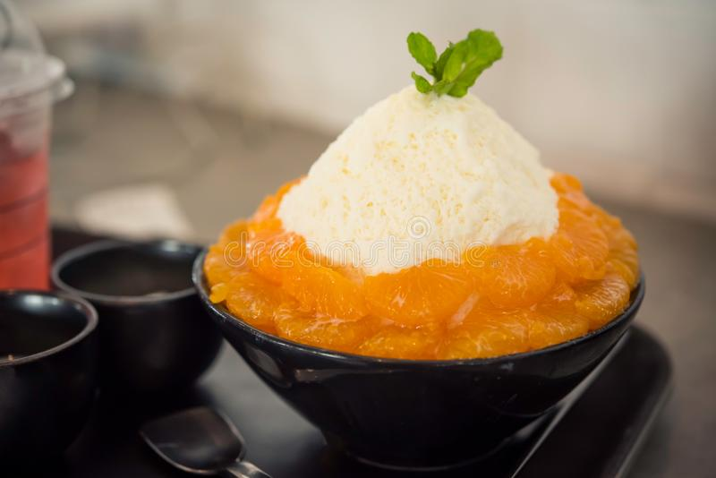 特写镜头橙色Bingsu冠上了与乳酪和酸奶冰淇凌双 免版税库存照片