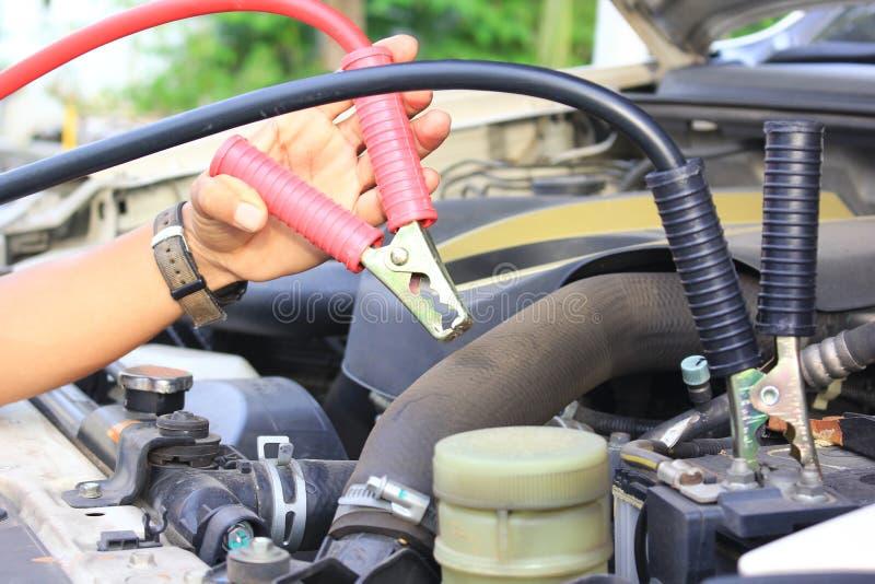 特写镜头汽车修理师使用电池跨接电线到汽车电池 免版税库存照片