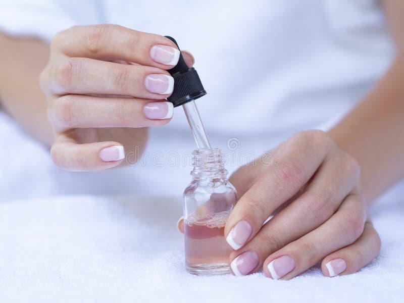 特写镜头法式修剪和被打开的指甲油瓶 妇女手关心 r 库存照片