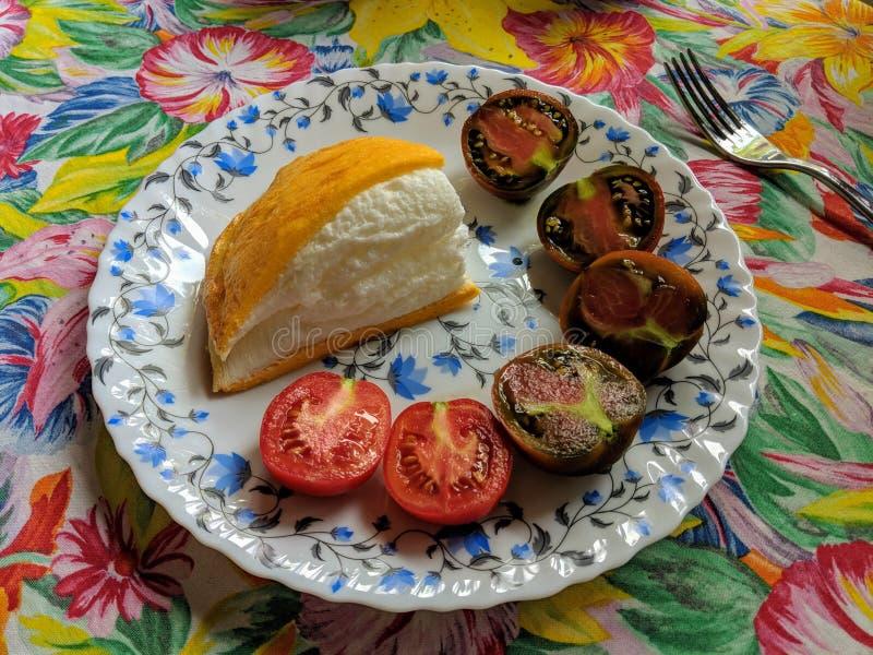 特写镜头煎蛋卷la肉鸡服务用在轻的白色板材的红色和棕色西红柿有蓝色花的,sta 免版税库存照片