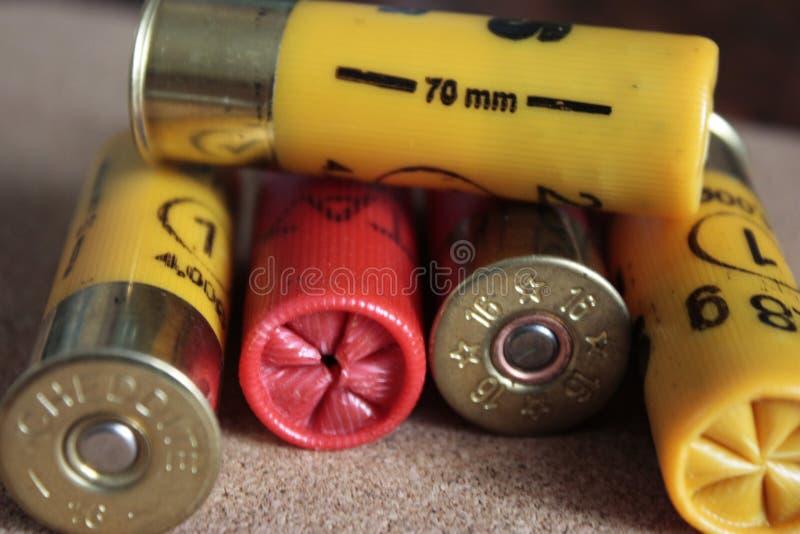 特写镜头猎枪或16口径猎枪弹药在黄色和红色木背景 库存图片