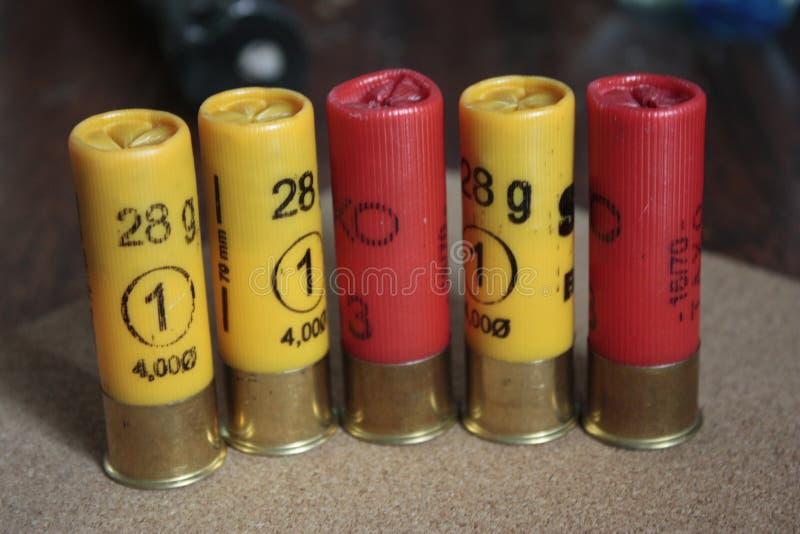 特写镜头猎枪或16口径猎枪弹药在黄色和红色木背景 免版税库存图片