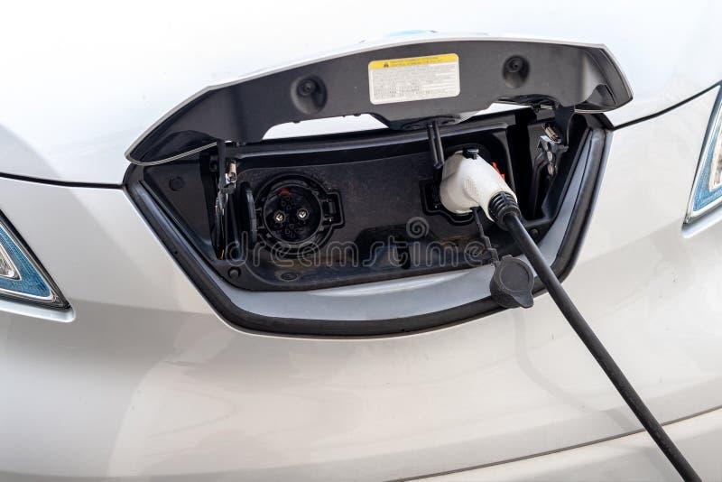 特写镜头现代电车pugged与快速的充电器在充电站在老欧洲城市的中心 友好的Ecol 库存图片