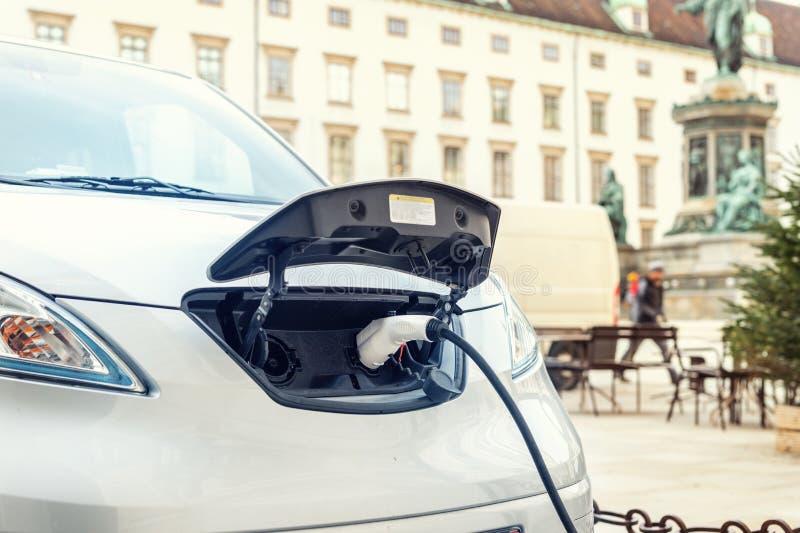 特写镜头现代电车pugged与快速的充电器在充电站在老欧洲城市的中心 Ecol友好的绿色 库存图片
