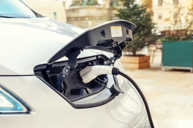 特写镜头现代电车pugged与快速的充电器在充电站在老欧洲城市的中心 Ecol友好的绿色 图库摄影