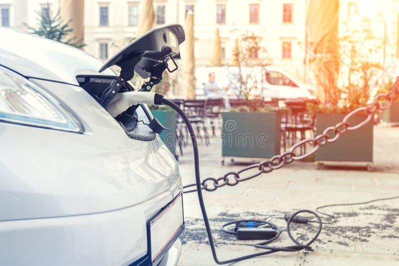 特写镜头现代电车pugged与快速的充电器在充电站在老欧洲城市的中心 Ecol友好的绿色 免版税图库摄影