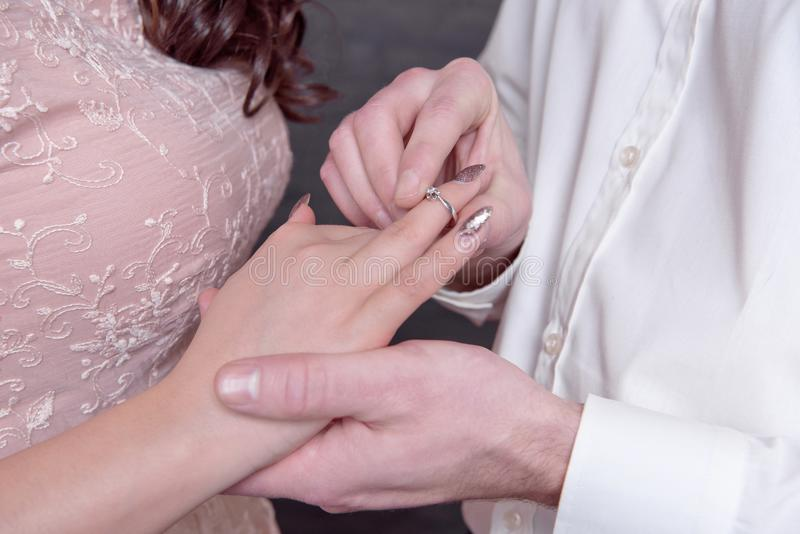 特写镜头男性和女性手,当投入圆环在结婚提议时的手指概念 图库摄影