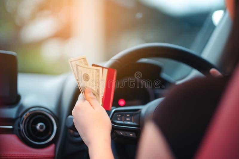 特写镜头画象坐在她新的白色汽车的手妇女显示信用卡和拿着美元个人运输购买 库存图片