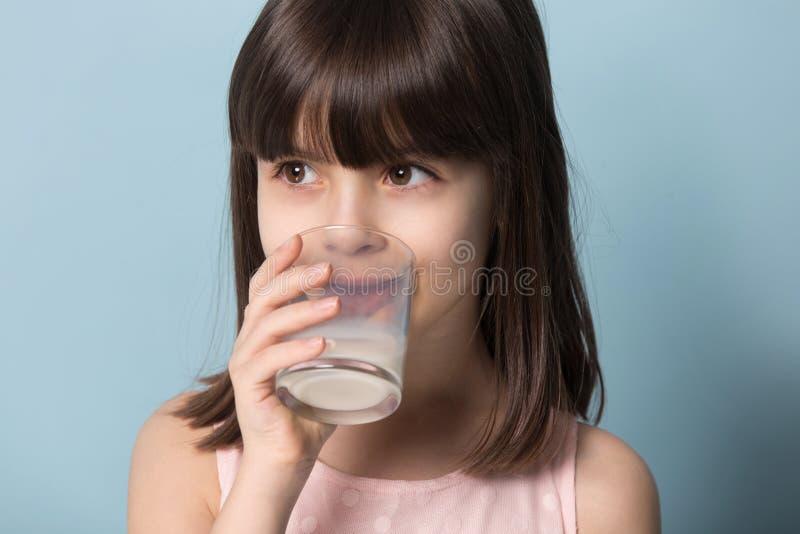 特写镜头画象女孩饮用奶在蓝色的演播室射击 免版税图库摄影