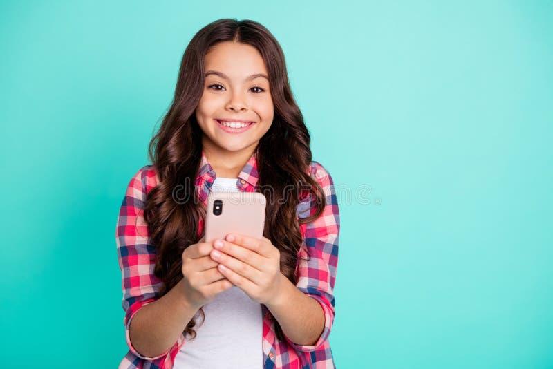 特写镜头画象她她好可爱的迷人的快乐的爽快有波浪头发的女孩在控制中举行在手上的衬衣 图库摄影