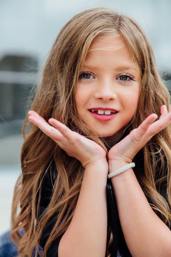 特写镜头画象情感女孩做鬼脸的美丽的女小学生孩子 背景儿童女孩相当少许模型操场 库存照片