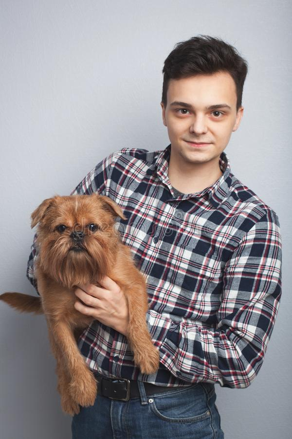 特写镜头画象英俊的年轻行家人,亲吻他的好朋友红色狗隔绝了轻的背景 正面人的情感, f 免版税库存照片