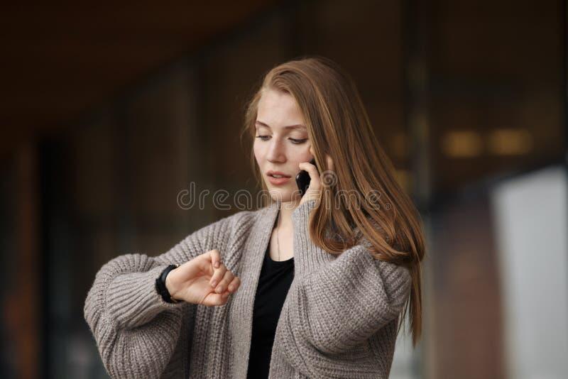 特写镜头画象,灰色西装燃烧物的少妇谈话在手机关注用尽时间  库存图片