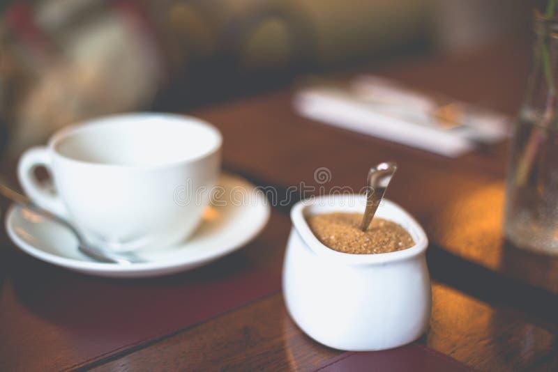 特写镜头白糖碗用在一个白色杯子的红糖有在桌上的一个茶碟的 免版税图库摄影