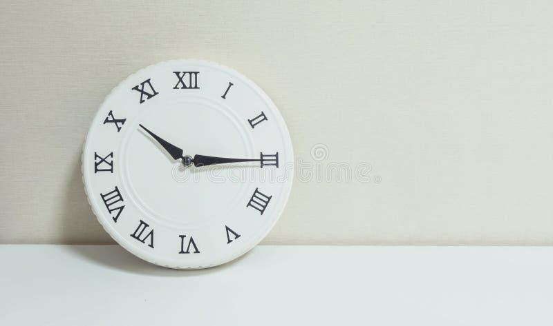 特写镜头白色时钟为装饰展示每处所通过十或10:15 a M 在白色木书桌和奶油上墙纸构造了背景 免版税图库摄影