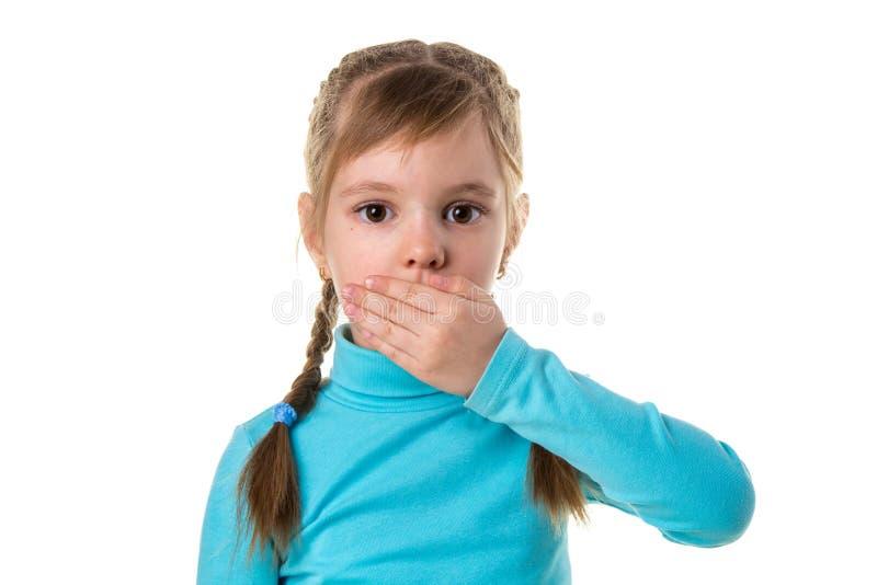 特写镜头盖她的嘴的害怕的女孩用在白色风景背景的手 库存图片