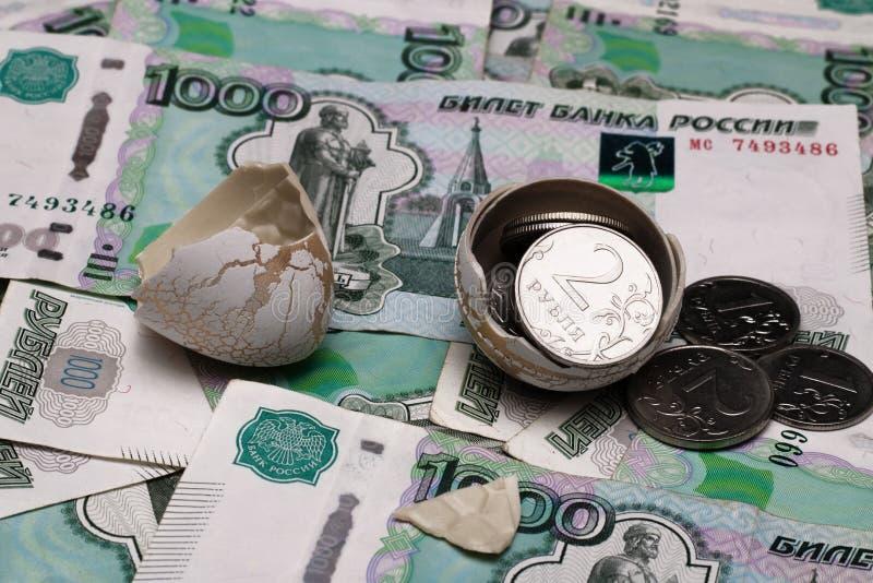 特写镜头硬币倾吐在蛋壳外面以纸票据一千,很多俄国金钱为背景, 库存图片