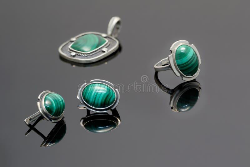 特写镜头秀丽银耳环、圆环和垂饰与绿沸铜在黑丙烯酸酯的书桌上 库存照片
