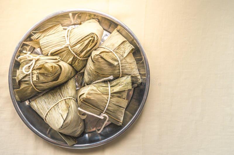 特写镜头糯米饺子或Zongzi在不锈钢盘子端午节的在奶油色颜色织品 致以对ance的尊敬 库存照片