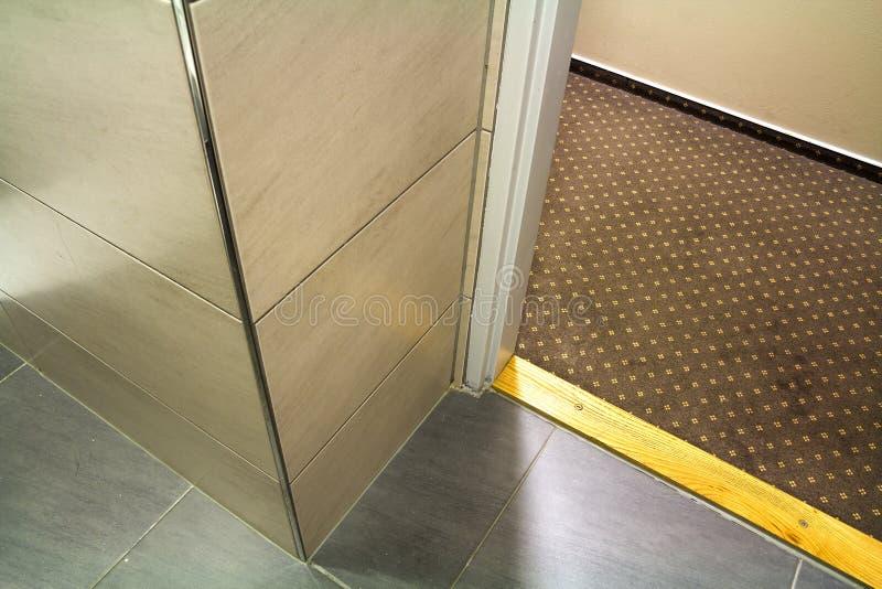 特写镜头细节,现代豪华空的卫生间的角落有地板的对天花板大理石陶瓷轻的米黄发光的瓦片 Professio 库存图片