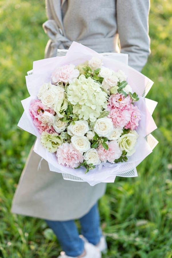 特写镜头美丽的春天花束在手上 与桃红色和绿色淡色的精美花的布置开花 草坪 库存图片