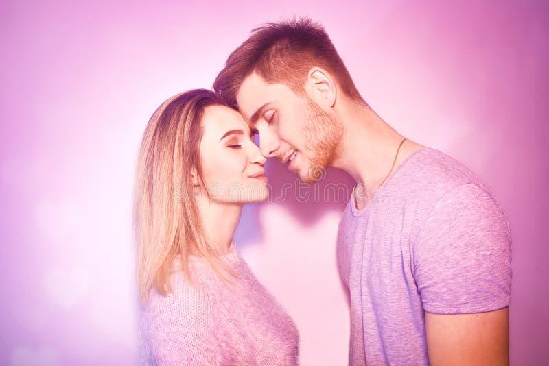 特写镜头美好夫妇亲吻 愉快的接触与他们的鼻子的人和女孩在桃红色背景中 爱的画象 免版税库存照片