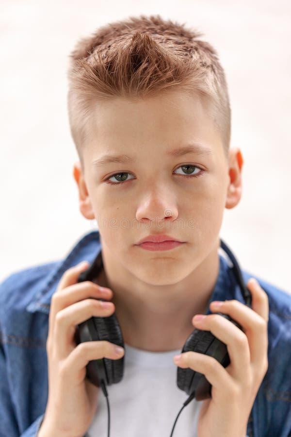特写镜头耳机的画象少年在白色背景 库存照片