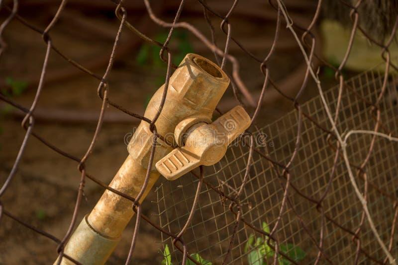 特写镜头肮脏的PVC阀门塑料管子-生锈的老铁丝网-被放弃的破烂物 库存照片