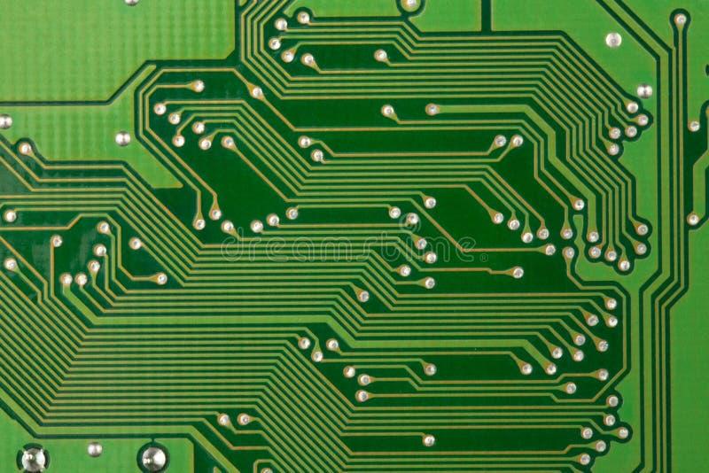 特写镜头背景的电路板绿色,那里是很多导电性轨道 库存照片