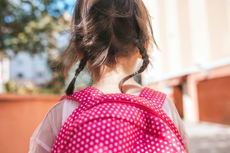 特写镜头背面图画象逗人喜爱女孩学龄前儿童摆在室外与桃红色背包反对被弄脏的大厦 愉快的孩子 免版税库存图片