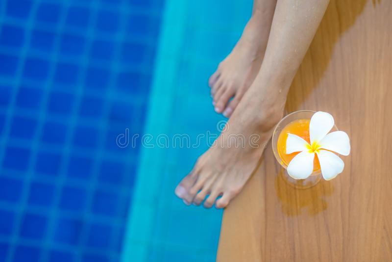 特写镜头腿临近与鸡尾酒的游泳池 图库摄影