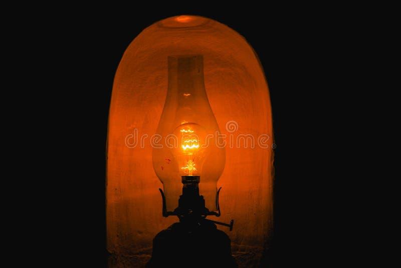 特写镜头被射击一盏被点燃的黑煤油灯在一个暗室 库存照片