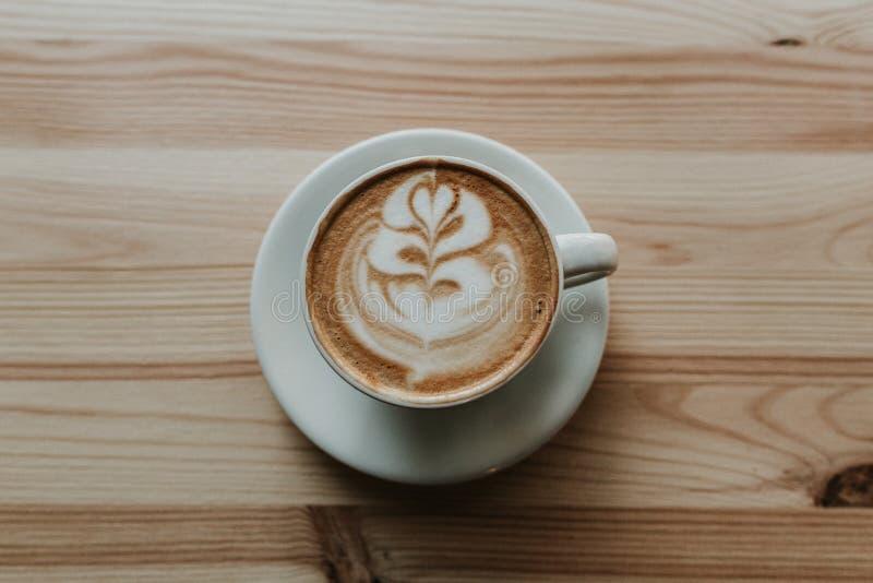 特写镜头被射击与拿铁艺术的咖啡在一张木桌上的白色陶瓷茶杯 免版税库存照片