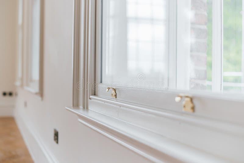 特写镜头被射击在一个白色窗口的一把金框格锁 图库摄影