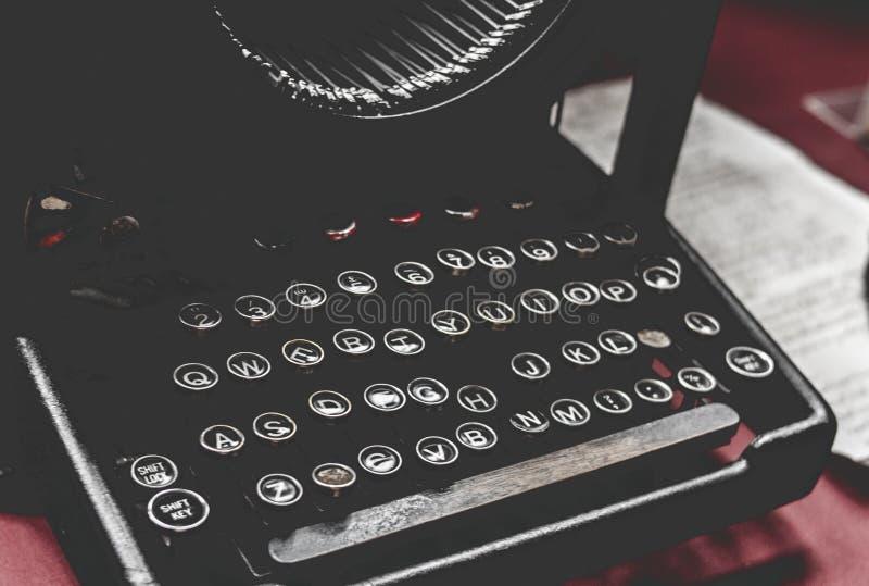 特写镜头被射击在一张红色书桌上的一台老葡萄酒打字机有在边的纸的 图库摄影