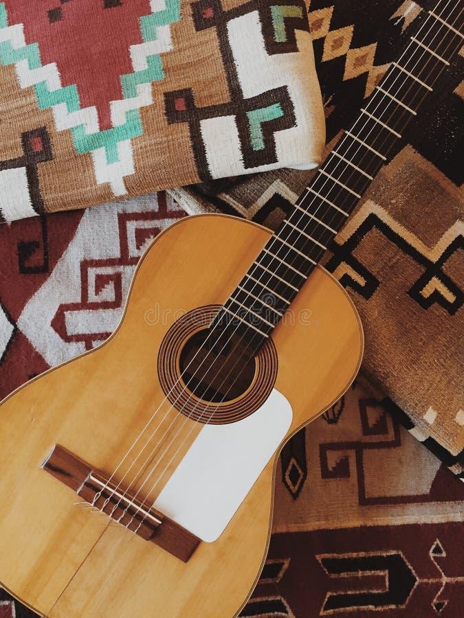 特写镜头被射击在一条被仿造的毯子的一把声学吉他 免版税库存照片