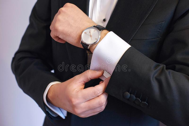 特写镜头被射击在半正式礼服的年轻白色白种人男性,固定他的袖扣 库存照片