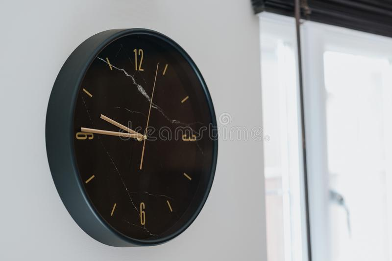 特写镜头被射击在白色墙壁上的一个黑时钟在一个现代房子里面 免版税库存照片