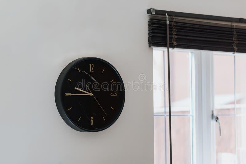 特写镜头被射击在白色墙壁上的一个黑时钟在一个现代房子里面 库存照片