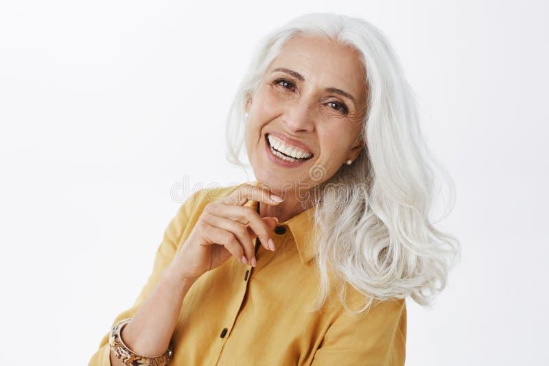 特写镜头被射击有白发的愉快的高兴和成功的迷人的欧洲年长女性在黄色军用防水短大衣 图库摄影
