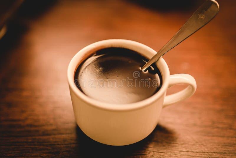 特写镜头被射击白色陶瓷浓咖啡杯子充满棕色木表面上的咖啡 库存照片