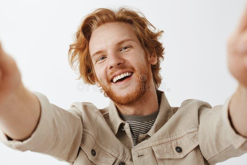 特写镜头被射击迷住有时髦的波浪发型的友好和无忧无虑的愉快的红头发人掀动从喜悦的人和胡子 库存图片