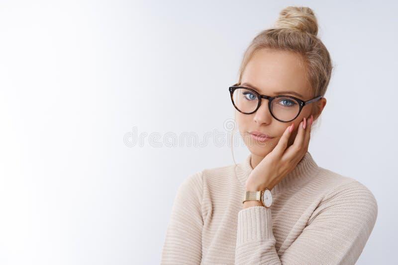 特写镜头被射击迷住有白肤金发的梳的头发的肉欲和梦想的年轻魅力妇女在戴时髦眼镜的小圆面包 免版税库存照片