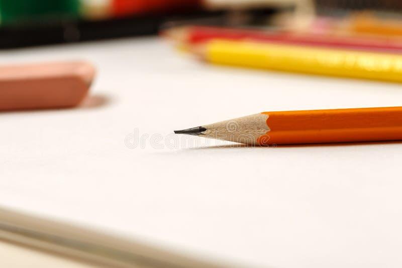 特写镜头被射击铅笔和橡皮擦在一张白色空白的纸片 免版税库存照片