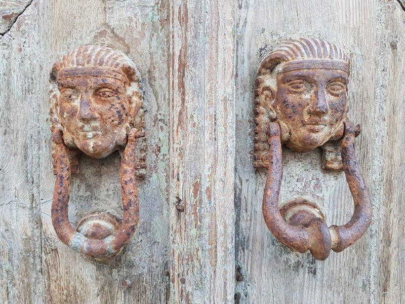 特写镜头装饰古老木材门的被射击美丽的被风化的敲门人 免版税库存图片