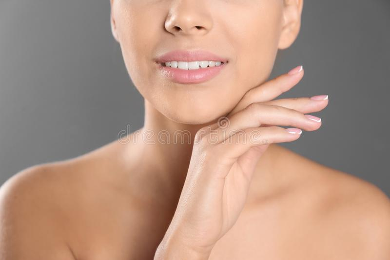 特写镜头观点的灰色背景的美丽的年轻女人 嘴唇塑造外形,皮肤护理和整容 免版税库存照片