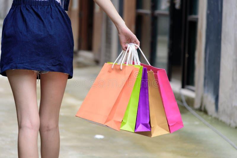 特写镜头视图亚裔女孩有拿着与商城和大厦背景的购物的五颜六色的袋子 库存照片